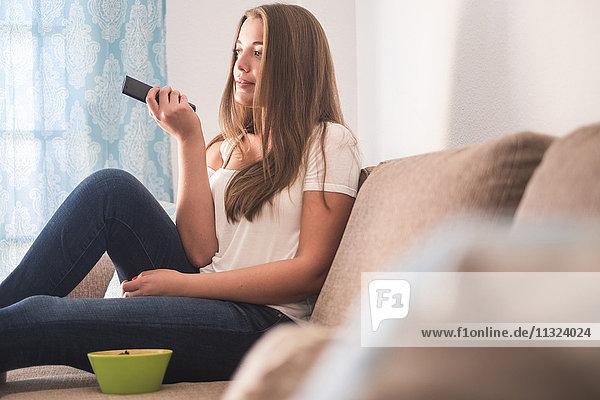 Junge Frau auf der Couch sitzend mit Fernbedienung fernsehend