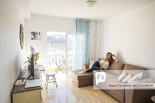 Junge Frau auf der Couch sitzend mit Fernbedienung