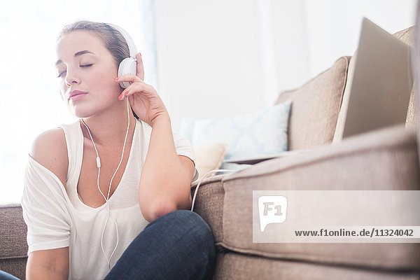 Junge Frau sitzt auf dem Boden des Wohnzimmers und hört Musik mit Kopfhörern. Junge Frau sitzt auf dem Boden des Wohnzimmers und hört Musik mit Kopfhörern.