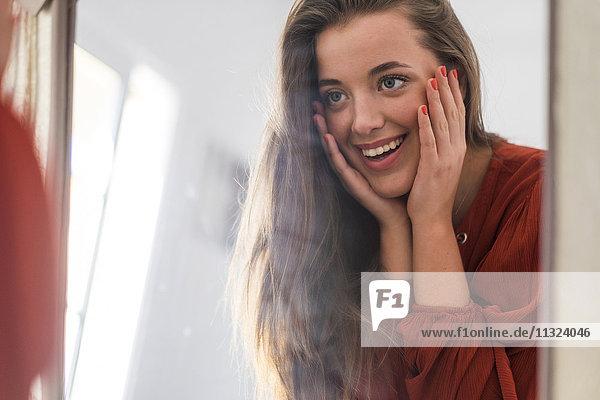 Spiegelbild einer glücklichen jungen Frau  die sich selbst ansieht.