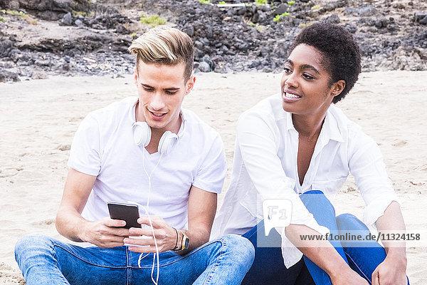 Junger Mann sitzend neben Freundin am Strand mit Handy und Kopfhörer