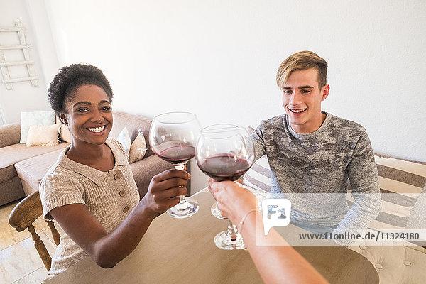 Junges Paar  das zu Hause mit Rotwein toastet. Junges Paar, das zu Hause mit Rotwein toastet.