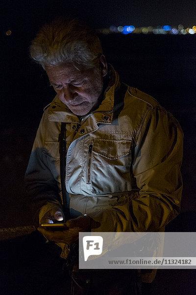 Ein älterer Mann  der nachts ein Handy benutzt.