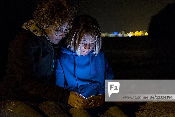 Mutter und Sohn telefonieren nachts mit dem Handy Mutter und Sohn telefonieren nachts mit dem Handy
