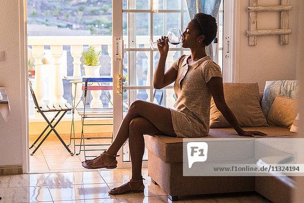 Junge Frau sitzt auf der Couch und trinkt ein Glas Rotwein.