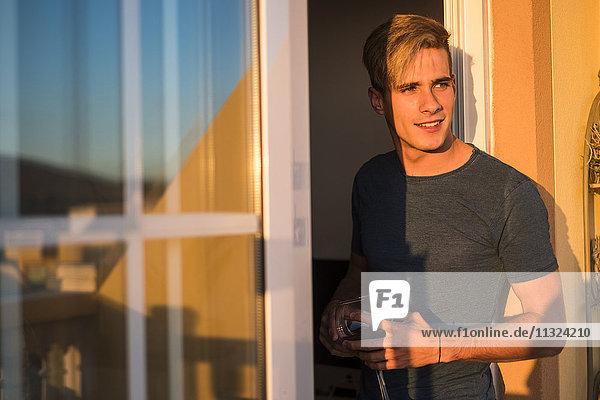 Porträt eines lächelnden jungen Mannes mit einem Glas Rotwein auf dem Balkon bei Sonnenuntergang