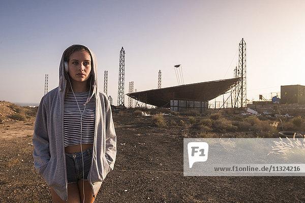 Spanien  Teneriffa  junge Frau in der Nähe eines verlassenen Flughafens mit Kopfhörern