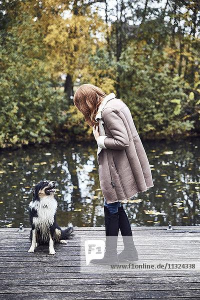 Frau mit ihrem Hund am Steg im Herbst