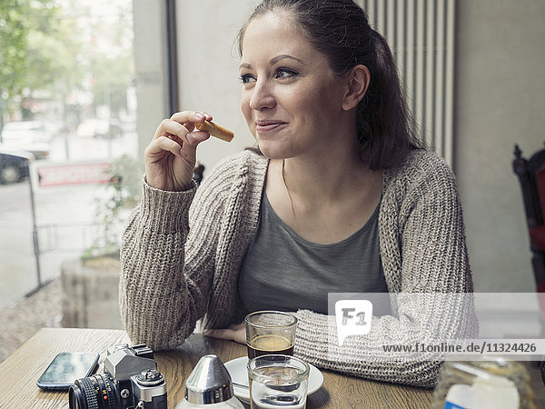 Lächelnde junge Frau mit Kamera im Cafe