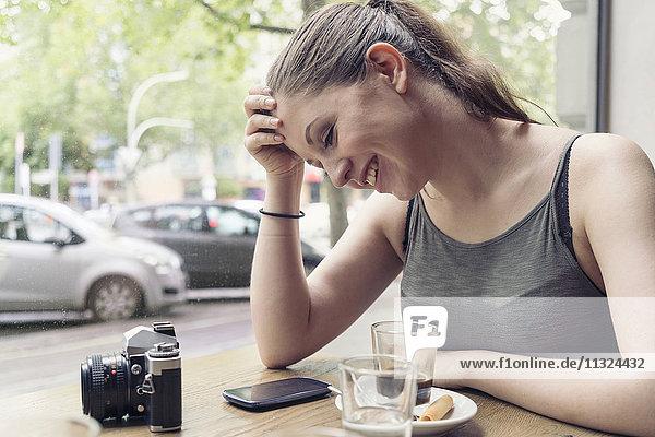 Lächelnde junge Frau in einem Café mit Kamera überprüft Handy