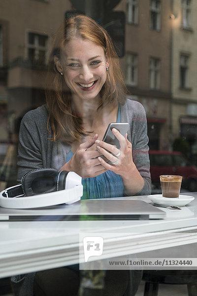 Porträt einer lächelnden Frau mit Smartphone im Café