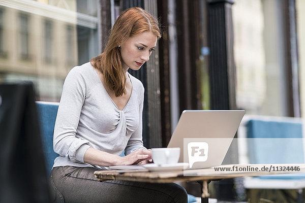 Redheaded Frau mit Laptop auf dem Bürgersteig Cafe