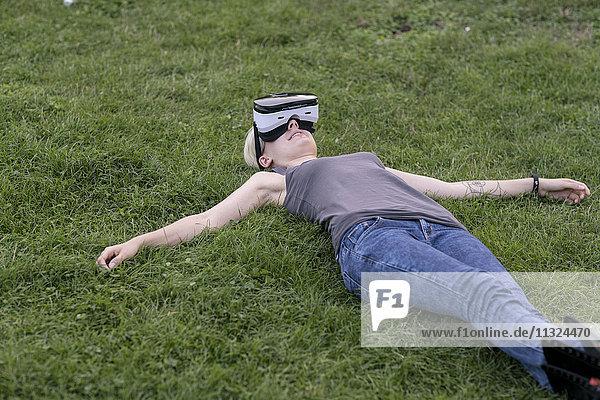 Junge Frau liegt auf einer Wiese und trägt eine Virtual Reality Brille im Freien.
