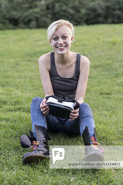 Porträt einer verblüfften jungen Frau auf der Wiese mit Virtual Reality Brille
