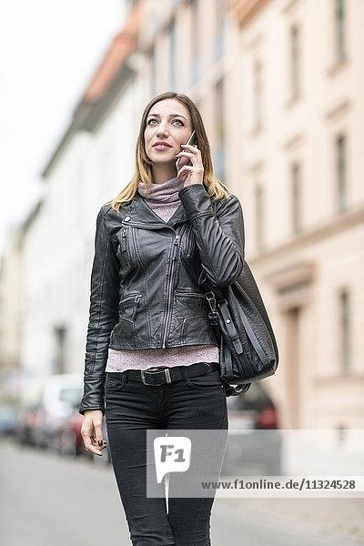 Junge Frau auf der Straße mit Smartphone