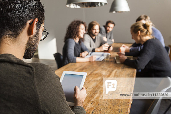 Young man using digital tablet in modern office with coworkers having a meeting in background