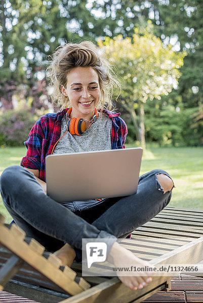 Porträt einer jungen Frau  die auf einer Liege im Garten sitzt und einen Laptop benutzt.