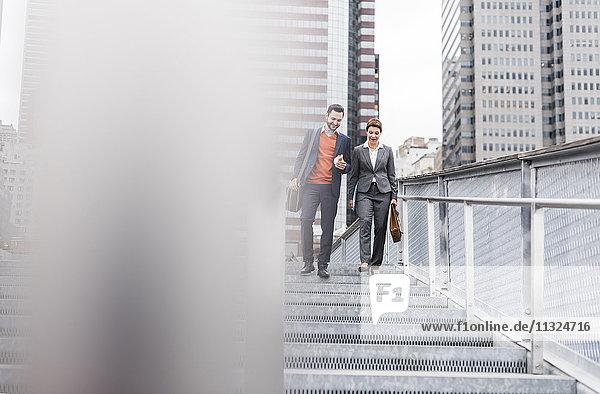USA  New York City  Geschäftsleute sprechen im Freien  während der Mann ein Sandwich hält.