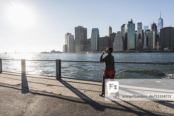 USA  Brooklyn  Geschäftsfrau beim Kaffeetrinken vor der Skyline von Manhattan