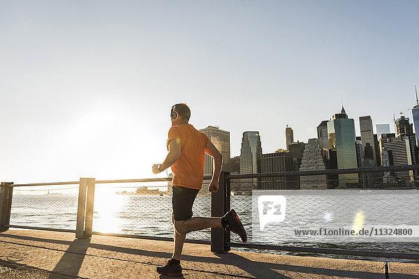 USA  Brooklyn  Mann joggen vor der Skyline von Manhattan am Abend