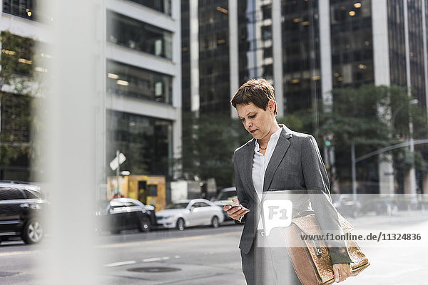 USA  New York City  businesswoman in Manhattan looking on cell phone