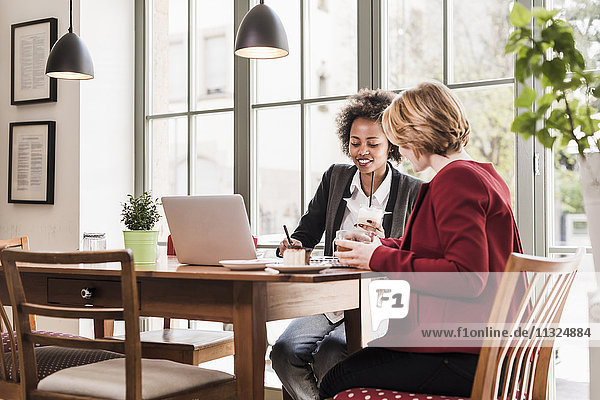 Zwei junge Frauen mit Laptop in einem Cafe