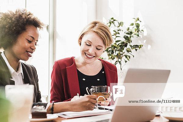 Zwei junge Frauen  die in einem Café arbeiten.