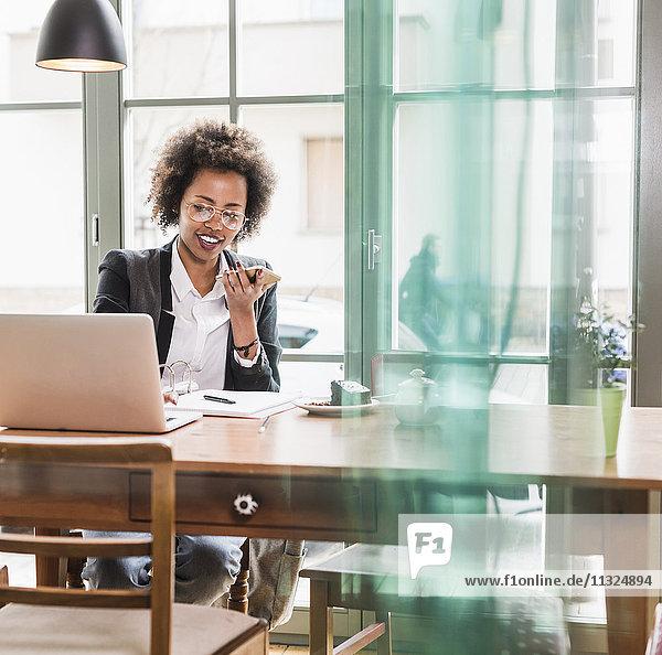 Junge Frau mit Handy und Laptop in einem Cafe