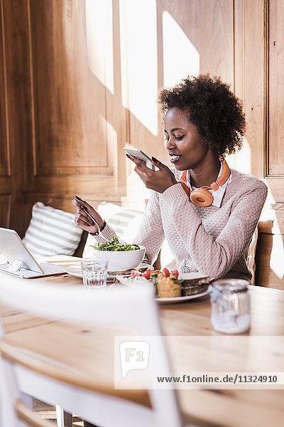 Junge Frau mit Handy und Tablette in einem Cafe