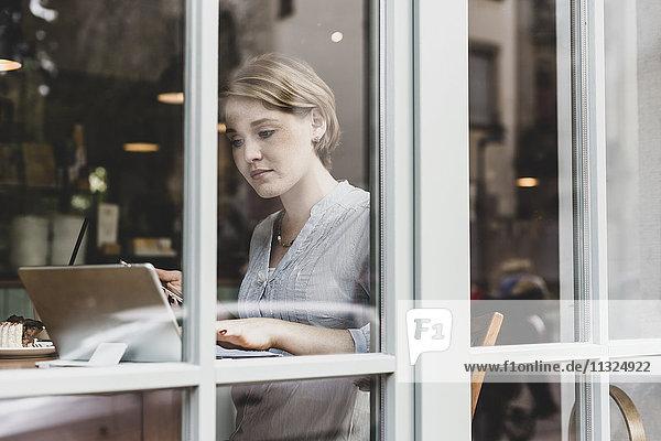 Junge Frau mit Handy und Tablette im Café