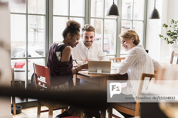 Drei junge Leute  die Tabletten in einem Café benutzen.