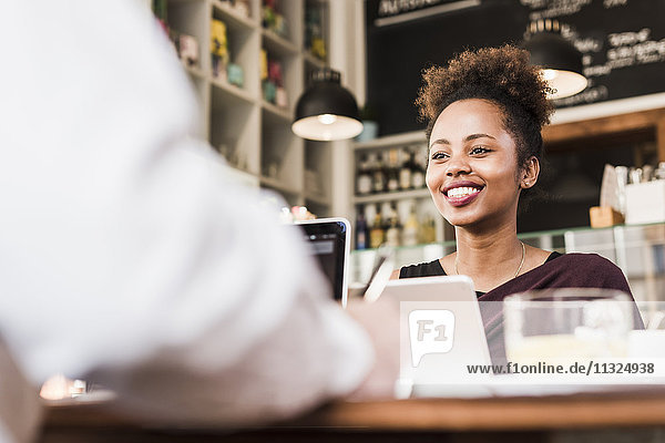 Waitress at counter in a cafe smiling at customer