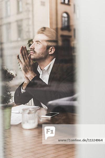 Ein junger Geschäftsmann denkt in einem Café.