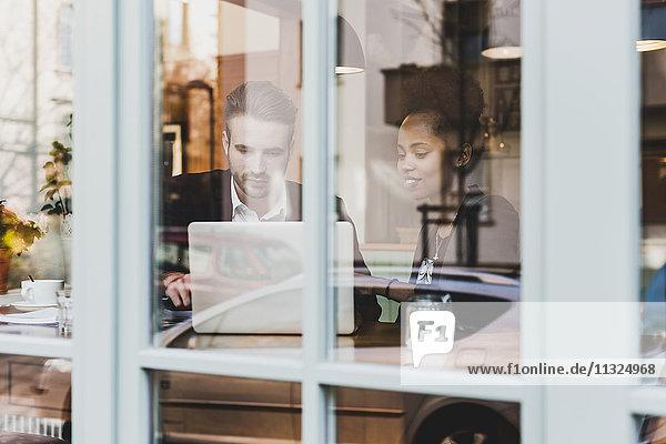 Junger Geschäftsmann und Frau mit Laptop im Café