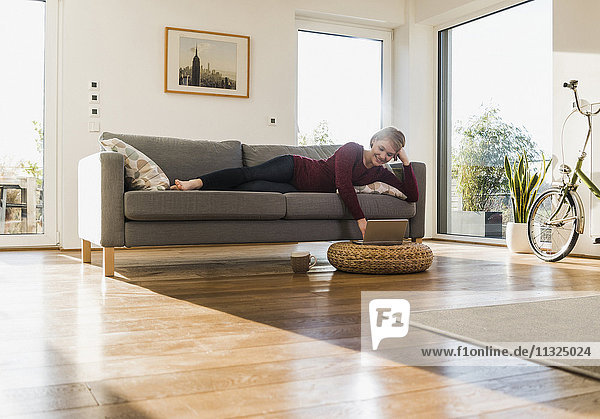 Smiling pregnant woman on couch using laptop