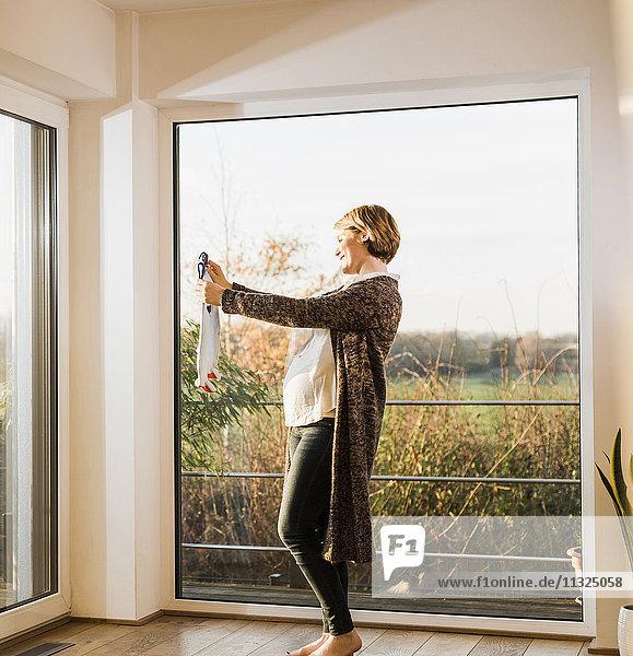 Schwangere Frau steht am Fenster und hält Babykleidung. Schwangere Frau steht am Fenster und hält Babykleidung.
