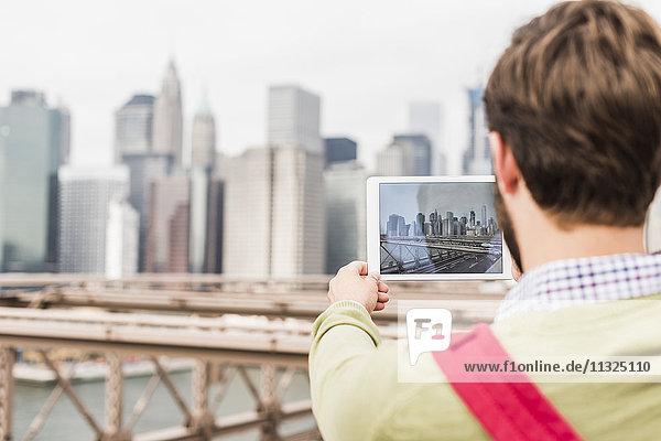 USA  New York City  Mann auf der Brooklyn Bridge beim Fotografieren von Tabletten