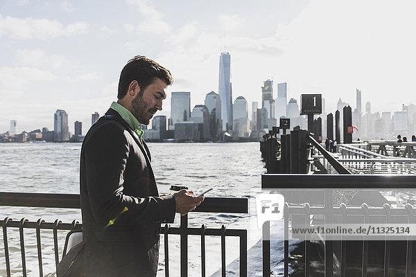 USA  Geschäftsmann mit Handy am New Jersey Waterfront mit Blick auf Manhattan USA, Geschäftsmann mit Handy am New Jersey Waterfront mit Blick auf Manhattan