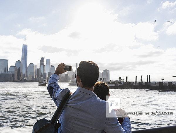 USA  Mann und Frau an der New Jersey Waterfront mit Blick auf Manhattan beim Fotografieren von Mobiltelefonen USA, Mann und Frau an der New Jersey Waterfront mit Blick auf Manhattan beim Fotografieren von Mobiltelefonen