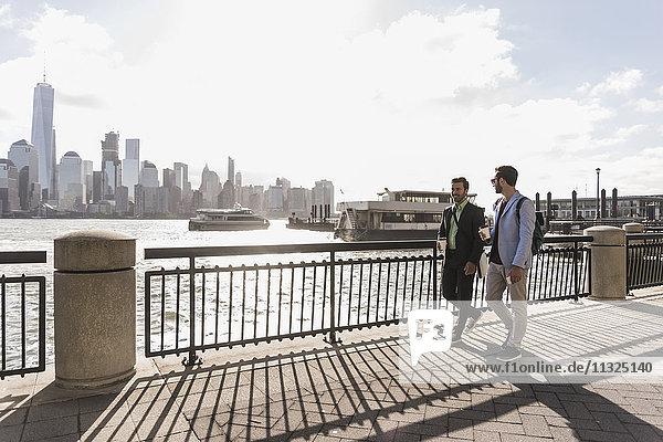 USA  zwei Geschäftsleute  die an der Waterfront von New Jersey mit Blick auf Manhattan spazieren gehen. USA, zwei Geschäftsleute, die an der Waterfront von New Jersey mit Blick auf Manhattan spazieren gehen.