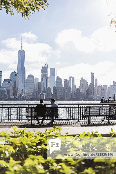 USA  zwei Geschäftsleute sitzen auf einer Bank an der New Jersey Waterfront mit Blick auf Manhattan USA, zwei Geschäftsleute sitzen auf einer Bank an der New Jersey Waterfront mit Blick auf Manhattan