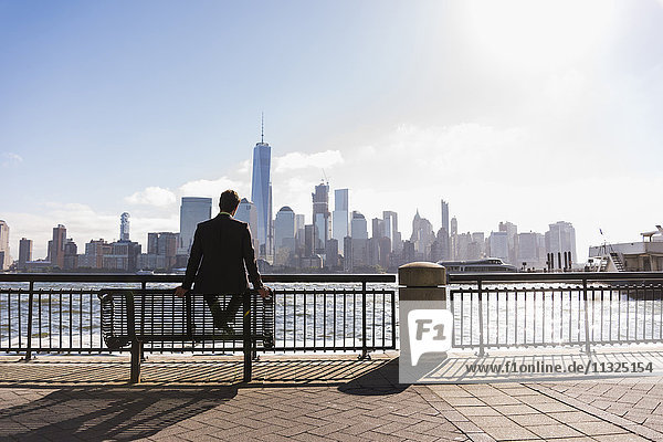 USA  Mann sitzt auf einer Bank am New Jersey Waterfront mit Blick auf Manhattan USA, Mann sitzt auf einer Bank am New Jersey Waterfront mit Blick auf Manhattan