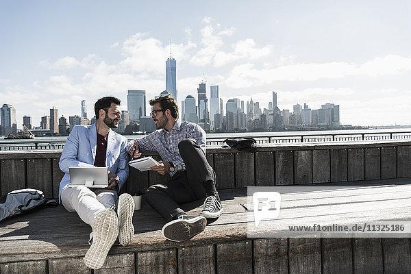 USA  zwei Geschäftsleute  die an der Waterfront von New Jersey mit Blick auf Manhattan arbeiten. USA, zwei Geschäftsleute, die an der Waterfront von New Jersey mit Blick auf Manhattan arbeiten.