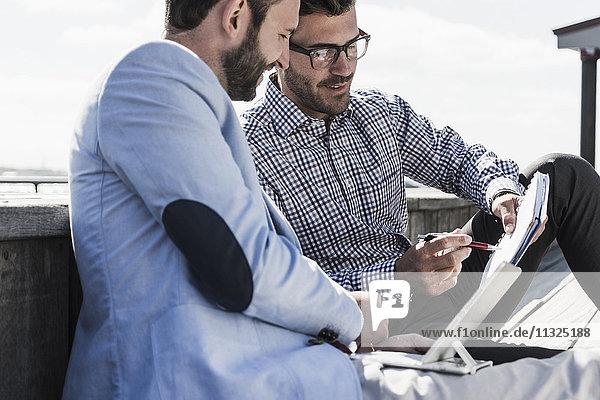Zwei Geschäftsleute mit Notizblock und Tablett im Außenbereich Zwei Geschäftsleute mit Notizblock und Tablett im Außenbereich