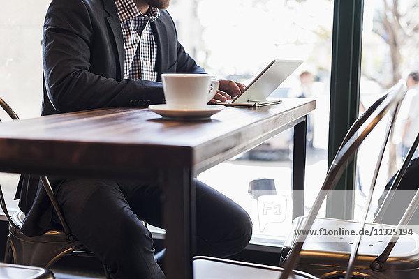 Nahaufnahme eines Geschäftsmannes mit Tablette in einem Cafe Nahaufnahme eines Geschäftsmannes mit Tablette in einem Cafe