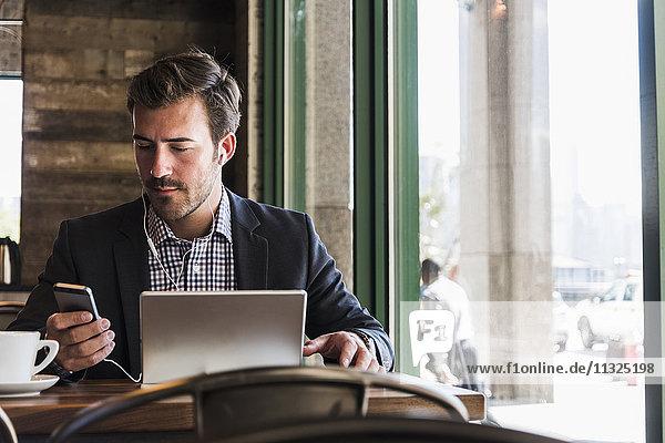 Geschäftsmann mit Tablette und Handy im Cafe Geschäftsmann mit Tablette und Handy im Cafe