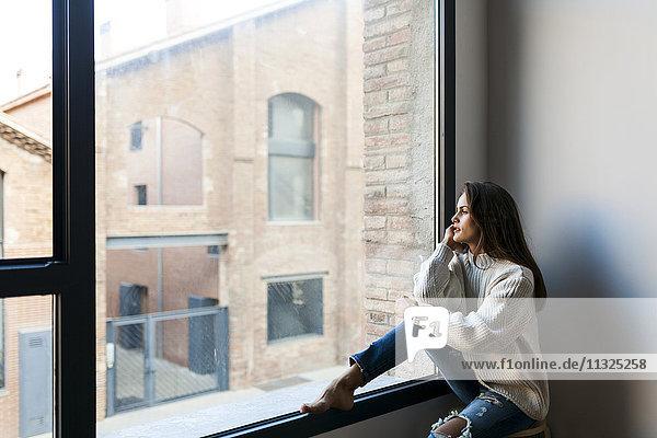 Junge Frau sitzt am Fenster und schaut hinaus.