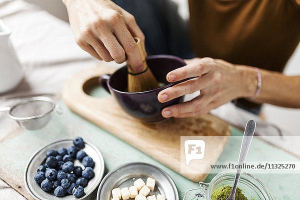 Frau bereitet Matcha Latte zu Hause vor