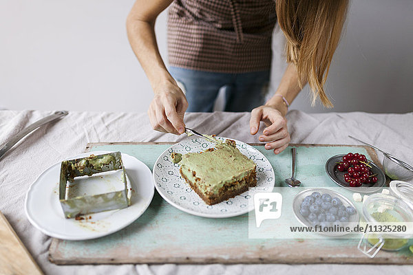 Frau bereitet veganen Matcha-Kuchen zu