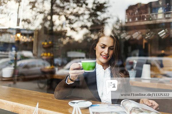 Lächelnde junge Frau in einem Café beim Lesen einer Zeitschrift